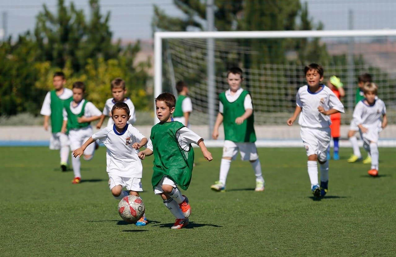 niños jugando futbol en estos tipos de canchas deportivas
